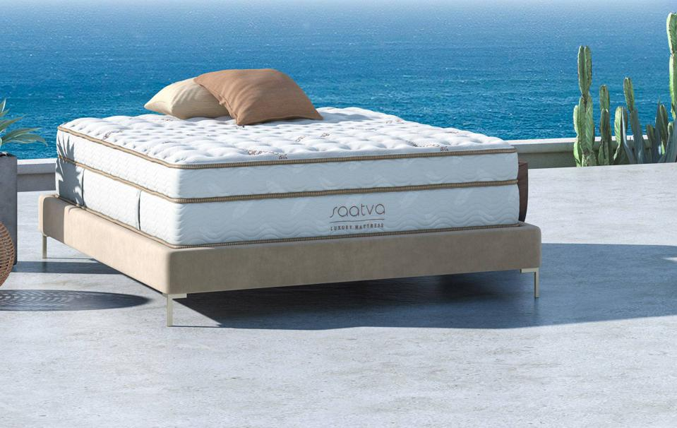 Saatva Classic mattress set up on a platform foundation in front of an ocean.