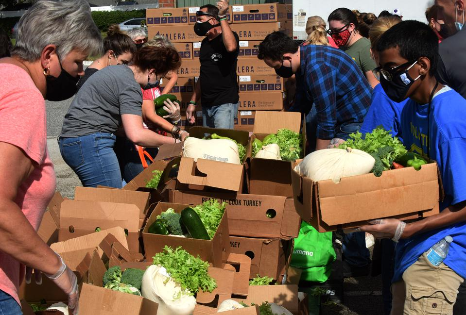 Volunteers distribute turkeys and other food assistance to...