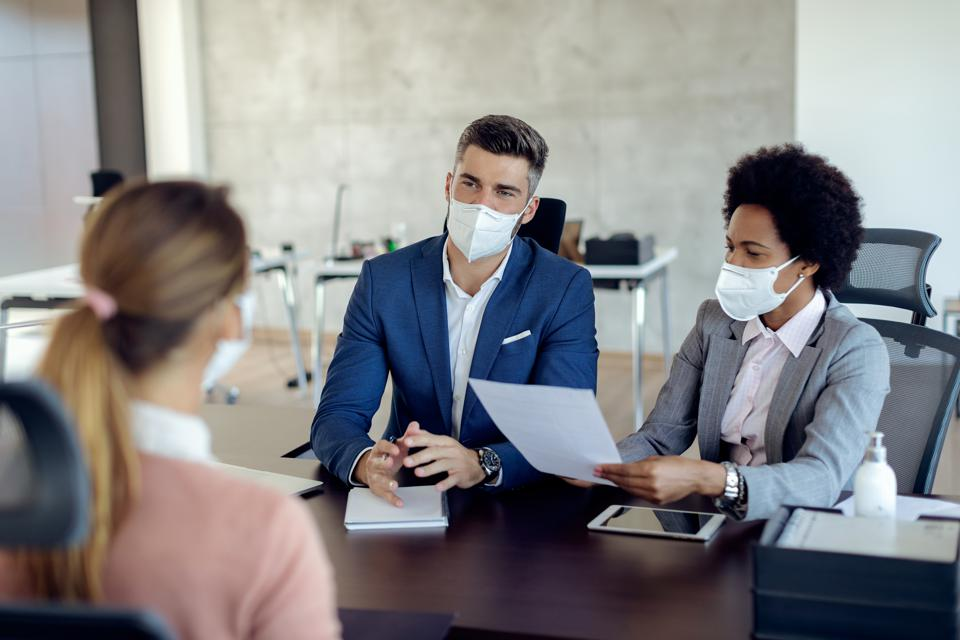 Business coworkers wearing face masks while talking to potential job candidate in the office.