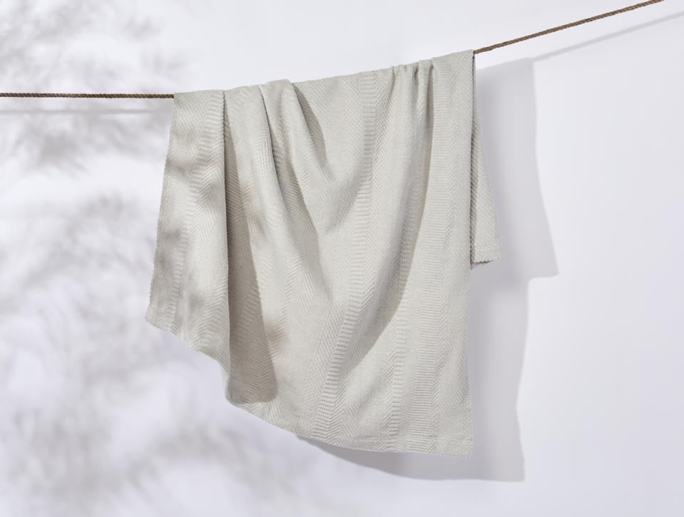 A recycled blanket hanging from a clothesline.