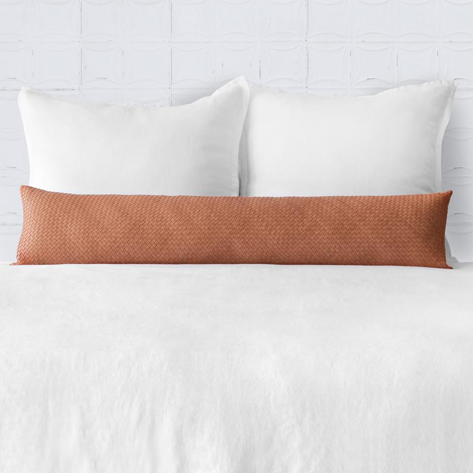 A long woven leather pillow on a bed.