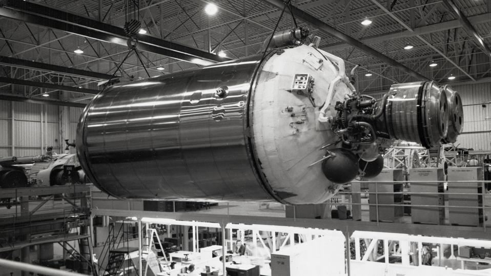 Black and white photo of a rocket stage hanging from a gantry above a factory floor.