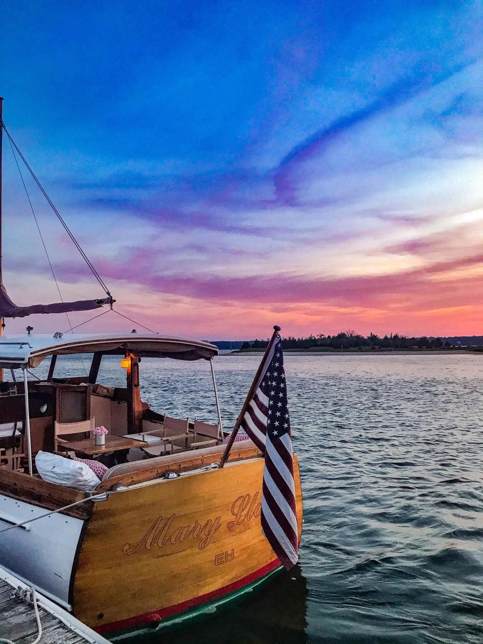 Boat in harbor at sunset with American flag.