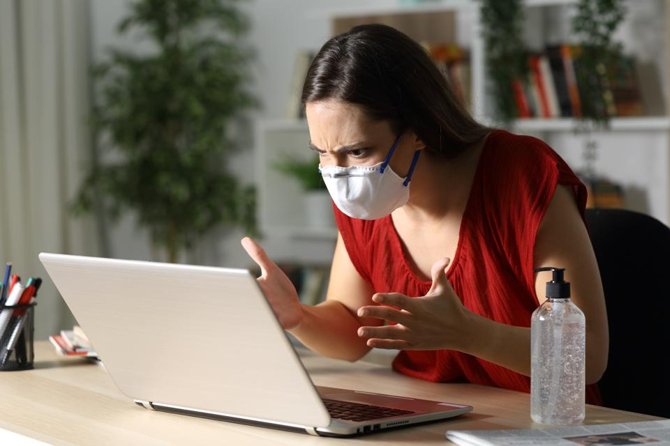 Angry woman at laptop masked and making hand gestures.