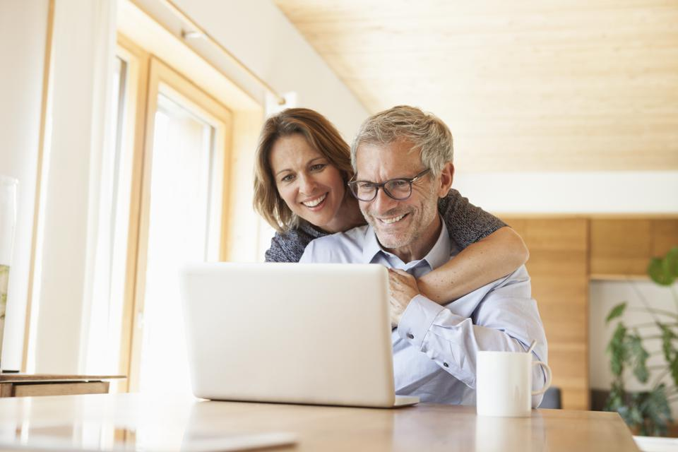 Happy mature couple sharing laptop at home