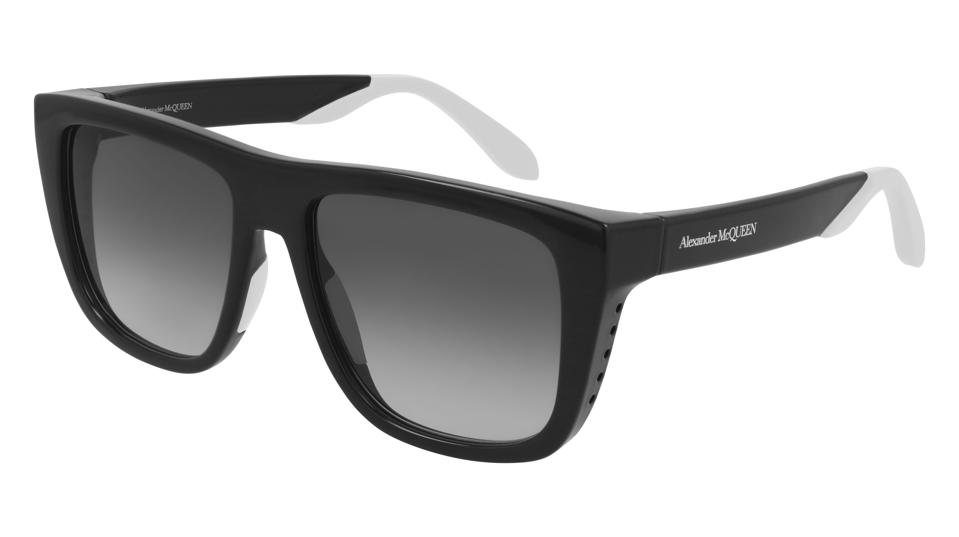 Shiny black acetate sunglasses in a visor shape fitted with gradient lenses, featuring white rubber nose pads and tips.