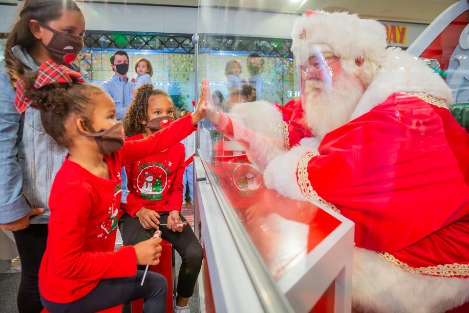 Children with reindeer masks meeting Santa