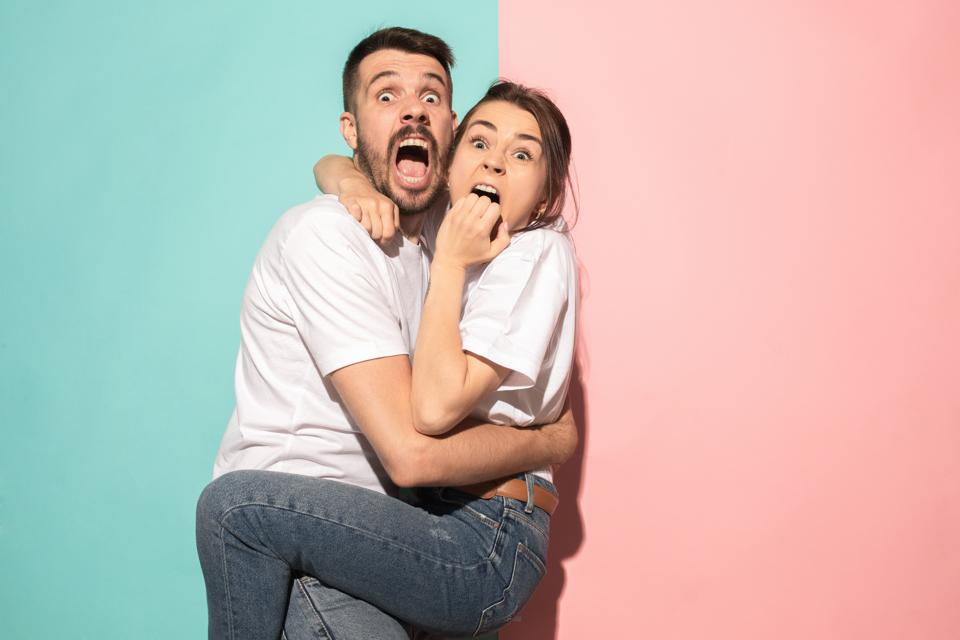 Portrait of the scared man and woman on pink and blue