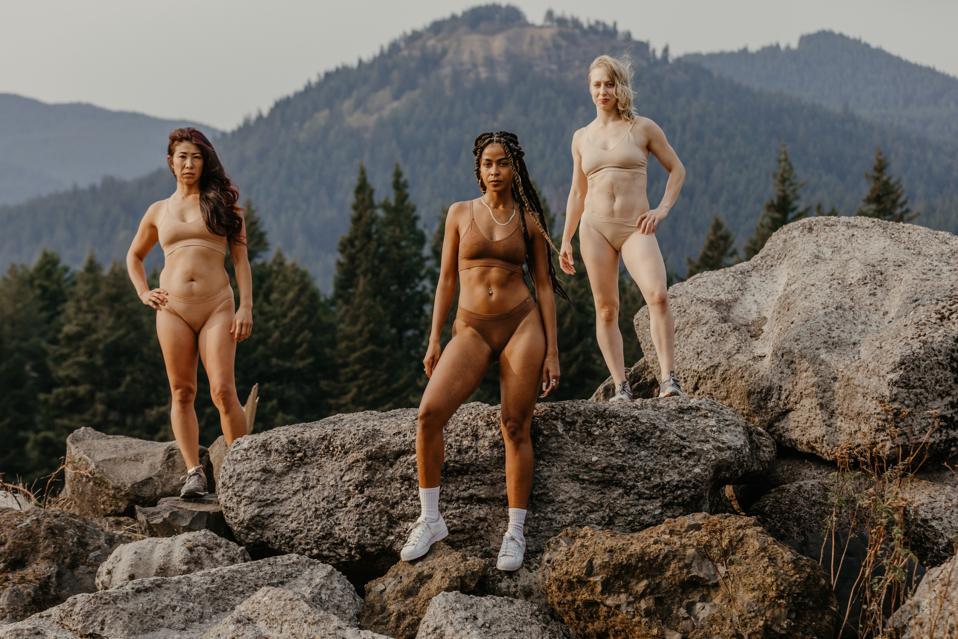 women in underwear on rock and mountain