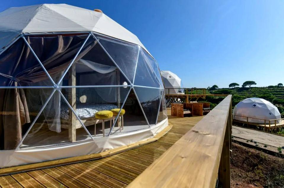 The domed tents near Lagoa de Santa André in Portugal sit on a wooden deck in the country.
