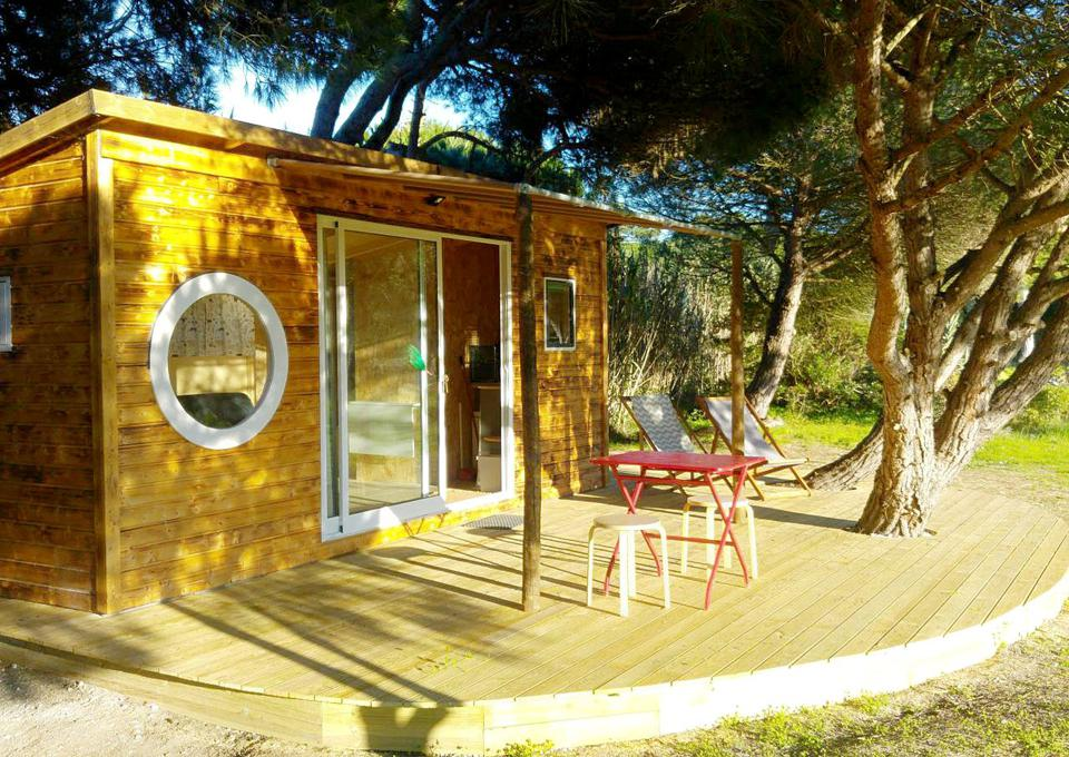 The cabin in Arrabida, Portugal, has a deck with a table and chairs beneath some trees.