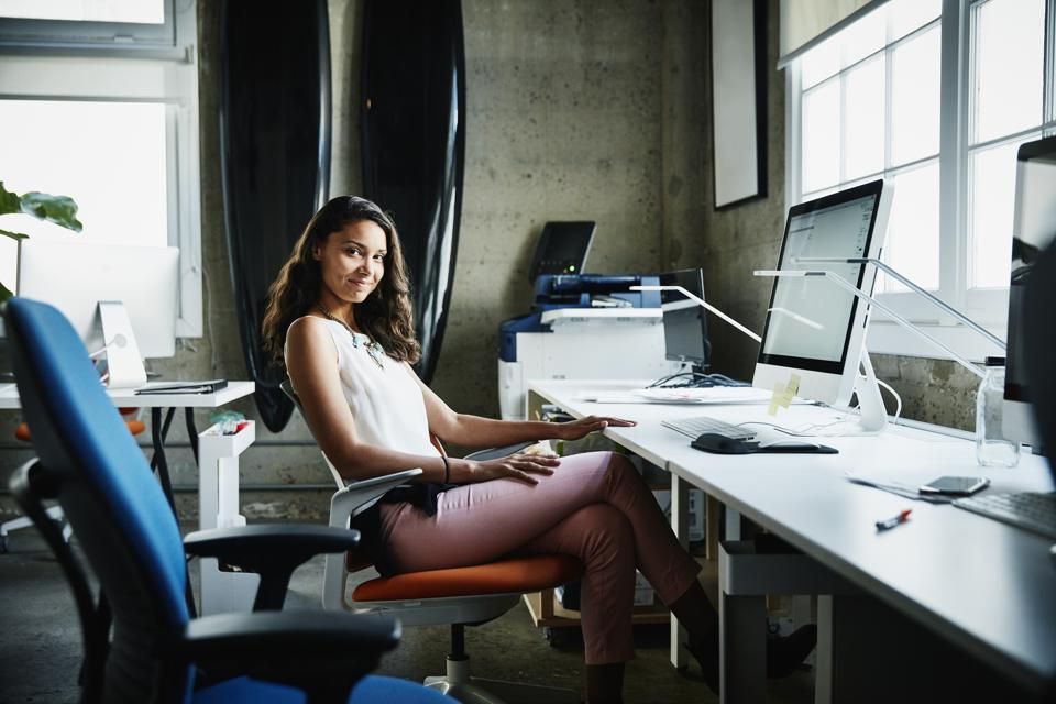 Portrait of smiling businesswoman at workstation in design office