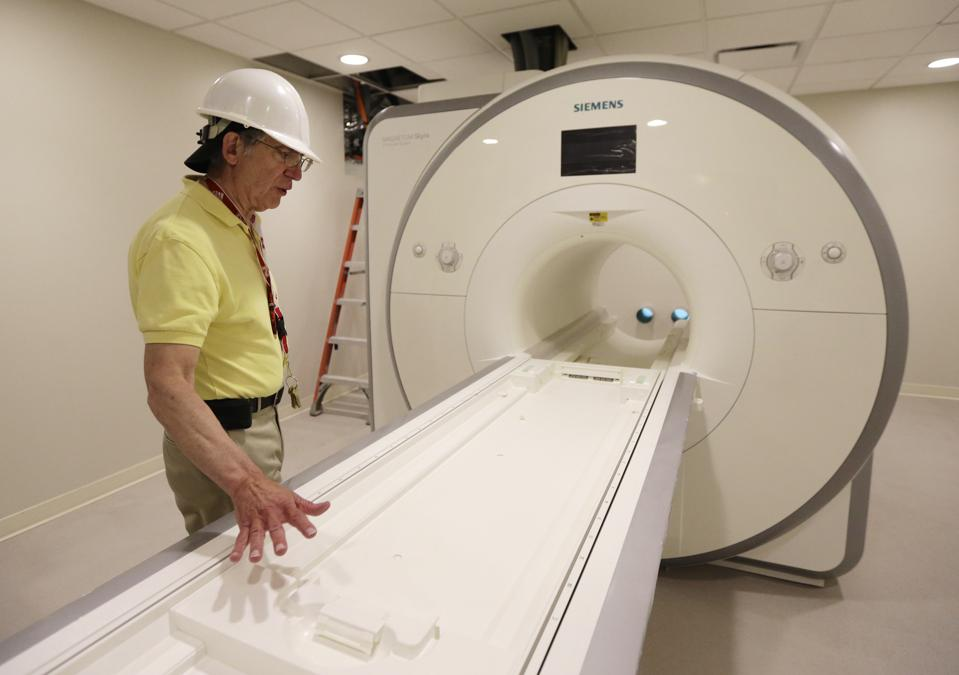 A worker looks over a newly-installed MRI machine.