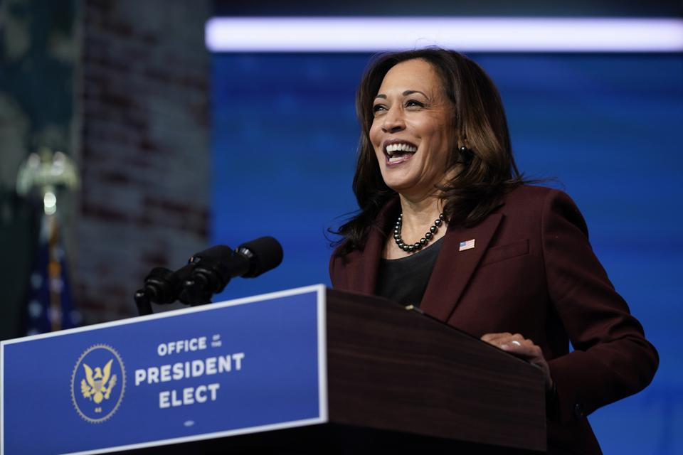 Vice President-Elect Kamala Harris smiling broadly while standing at a podium.