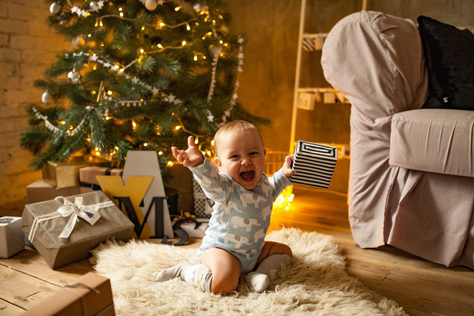 Little baby boy is happy with Christmas gift.