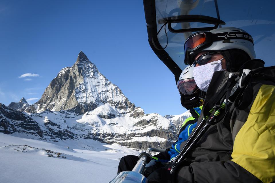 Skiers wearing masks, ride a ski lift at the Matterhorn in Zermatt in the Swiss Alps