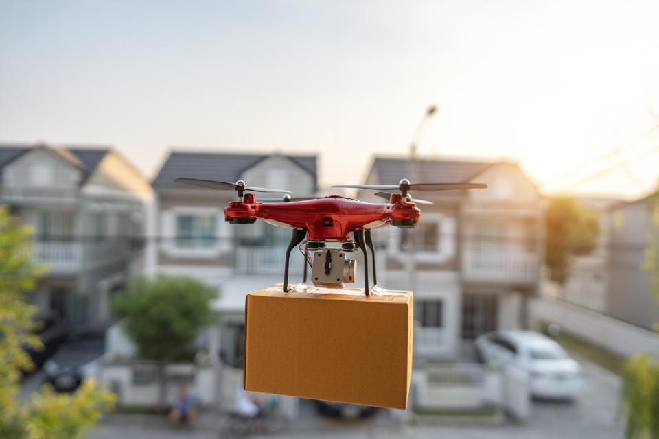 On 23 February 2020, Bangkok, Thailand Delivery drone carrying urgent shipment box in a city.