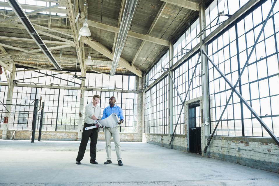Businessmen reading blueprints in empty warehouse