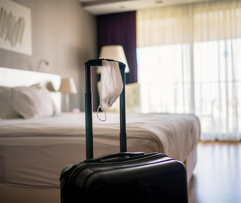 Face Mask and Suitcase in the Hotel Room