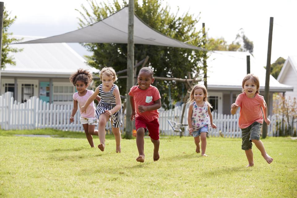 Children At Montessori School Having Fun Outdoors During Break