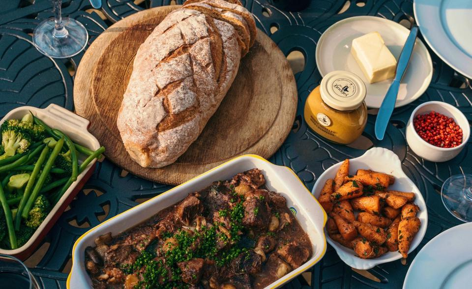 beef dish, carrots, green vegetables, mustard and bread