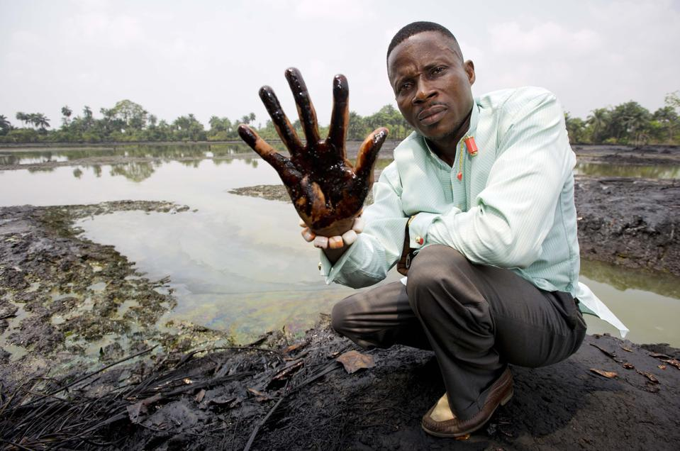 Nigerian farmer Eric Dooh shows his hand covered with oil found in his fish pond.