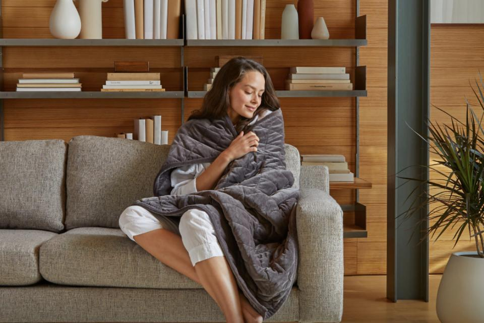Woman sitting on the couch wrapped up in a Saatva weighted blanket in gray.
