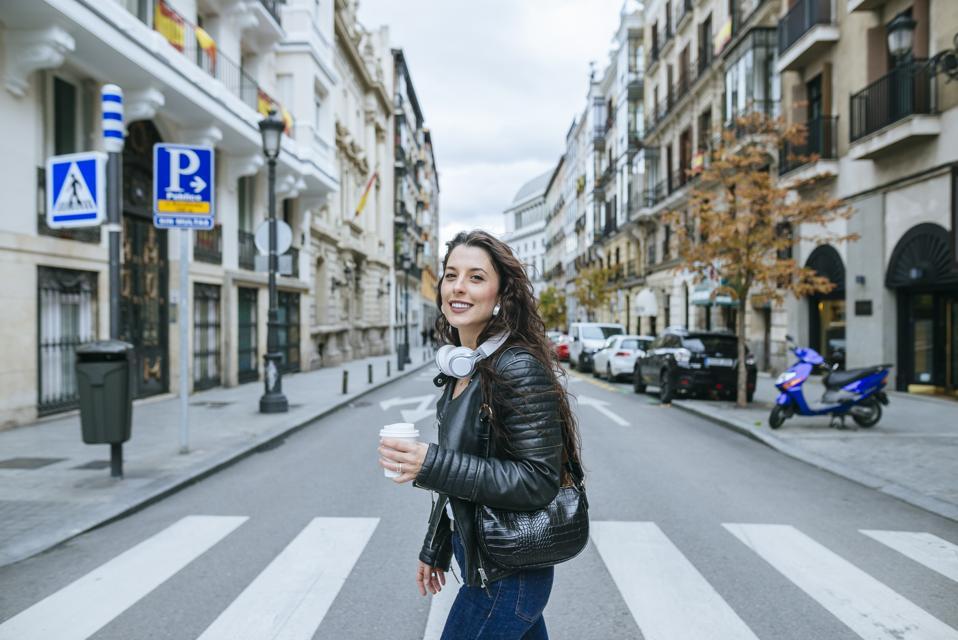 Woman crossing crosswalk with takeaway coffee