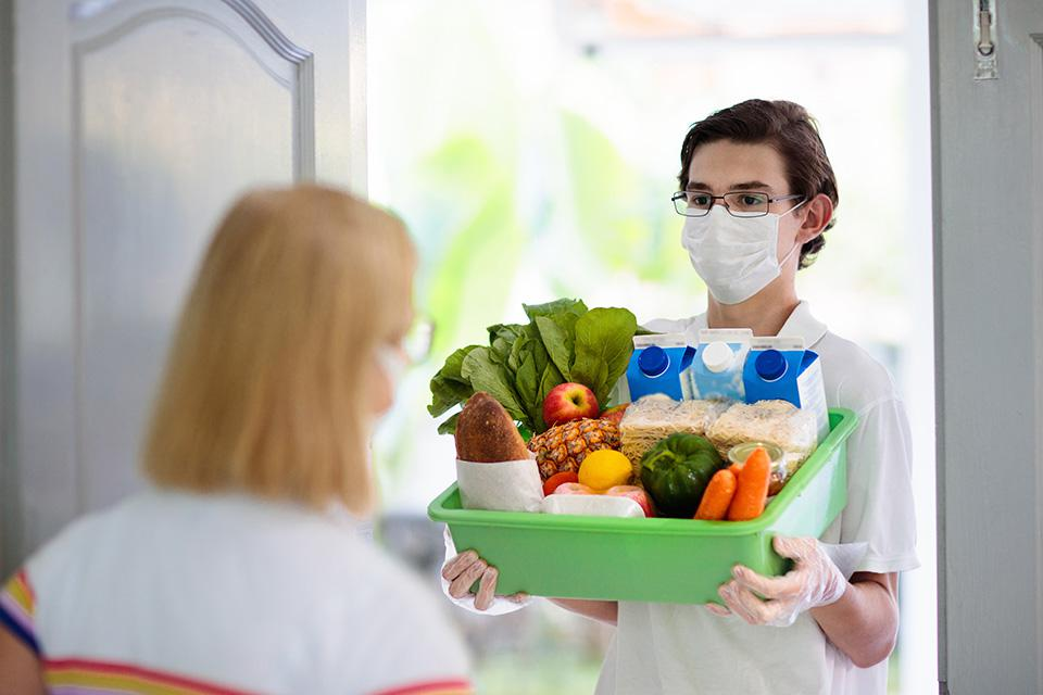 Delivery person bringing grocery order to door of customer