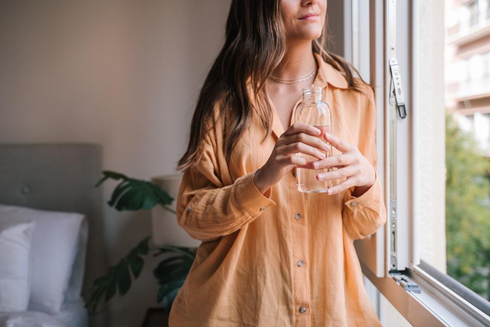 Midsection Of Young Woman Holding Water Bottle By Glass Window At Home