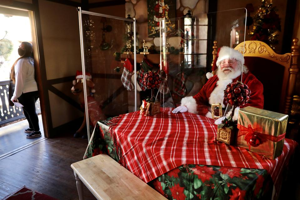 A Santa Claus behind plexiglass in Los Angeles County, Nov. 30 as a stay-at-home order took effect