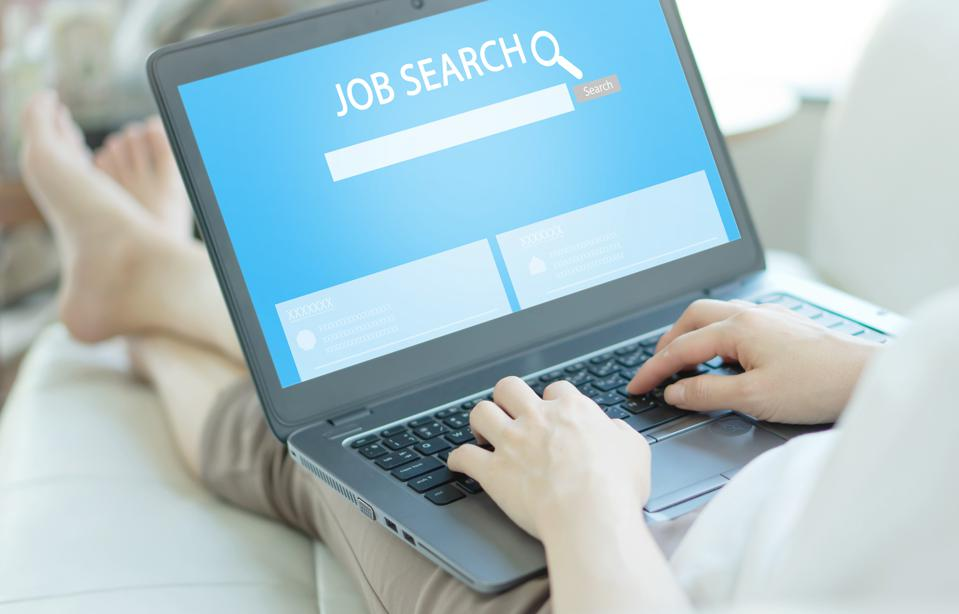 Woman trying to find work with online job search engine on laptop