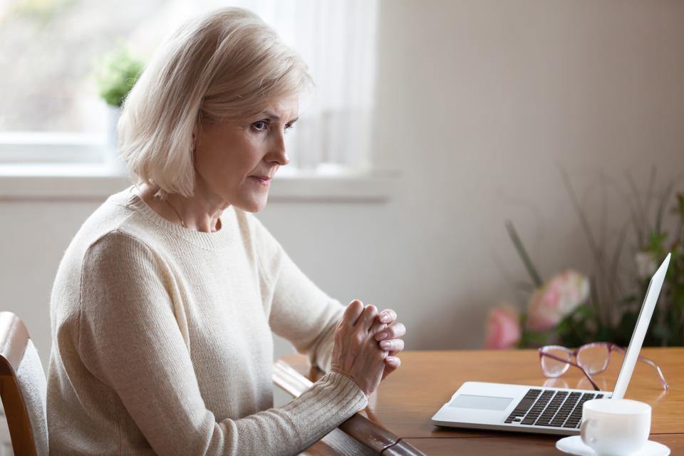 Thoughtful aged female considering something making decision