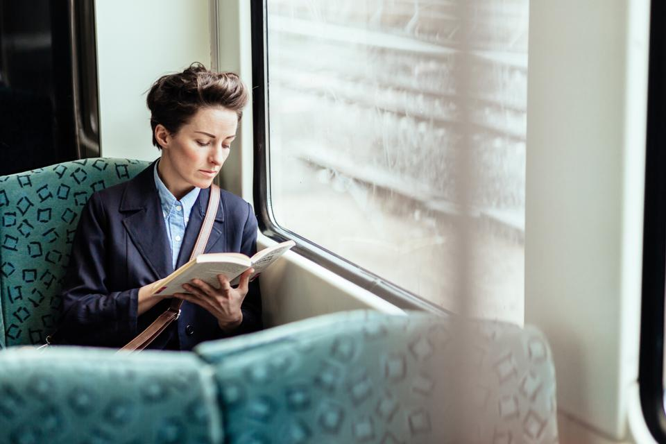 A businesswoman read a book while riding train.