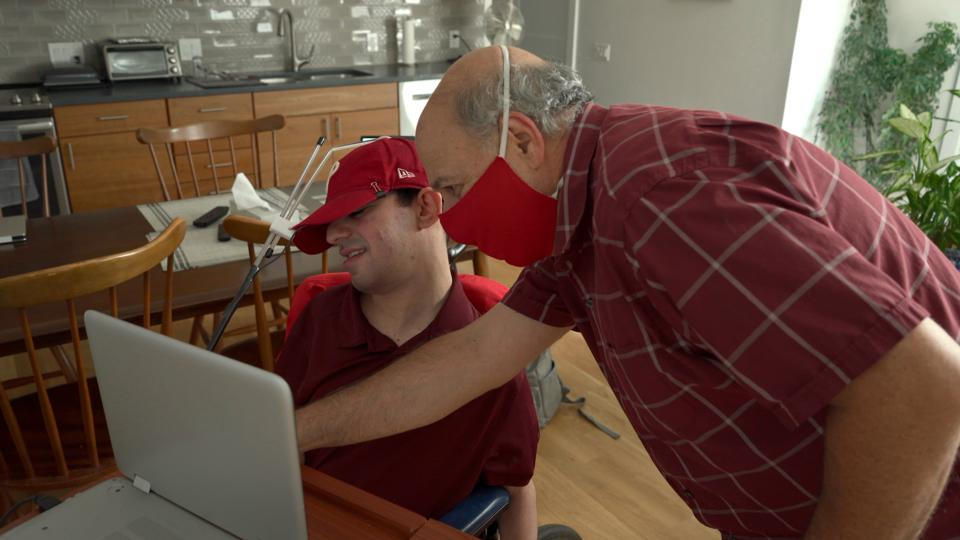 Nat Gupp sits in his chair in front of his laptop, with his dad leaning over to help