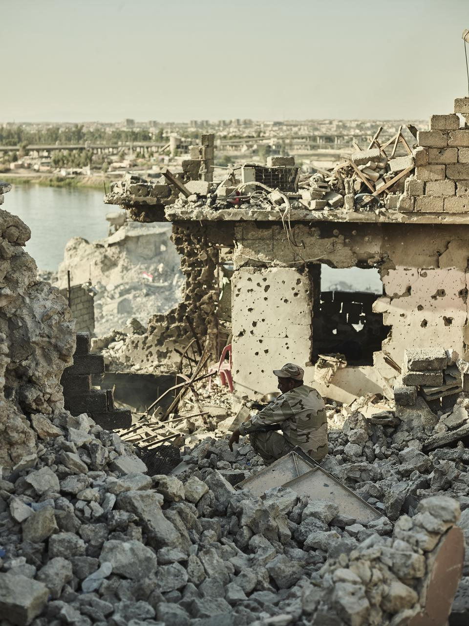 An Iraqi soldier looks on at the destruction along the...