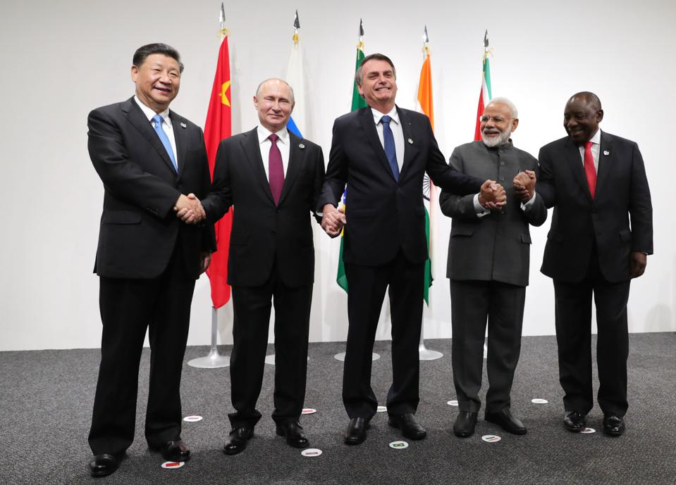 (From left) Chinese President Xi Jinping, Russian President Vladimir Putin, Brazilian President Jair Bolsonaro, India's Prime Minister Narendra Modi and South African President Cyril Ramaphosa shake hands as they pose in Japan for the 2019 G20 meeting.
