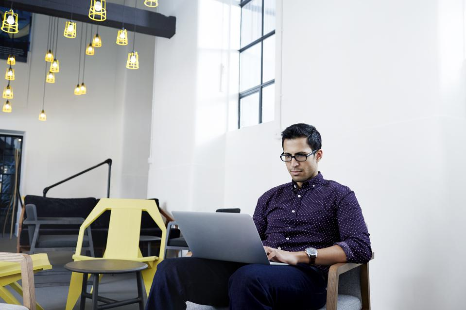 Young businessman using a laptop in modern office
