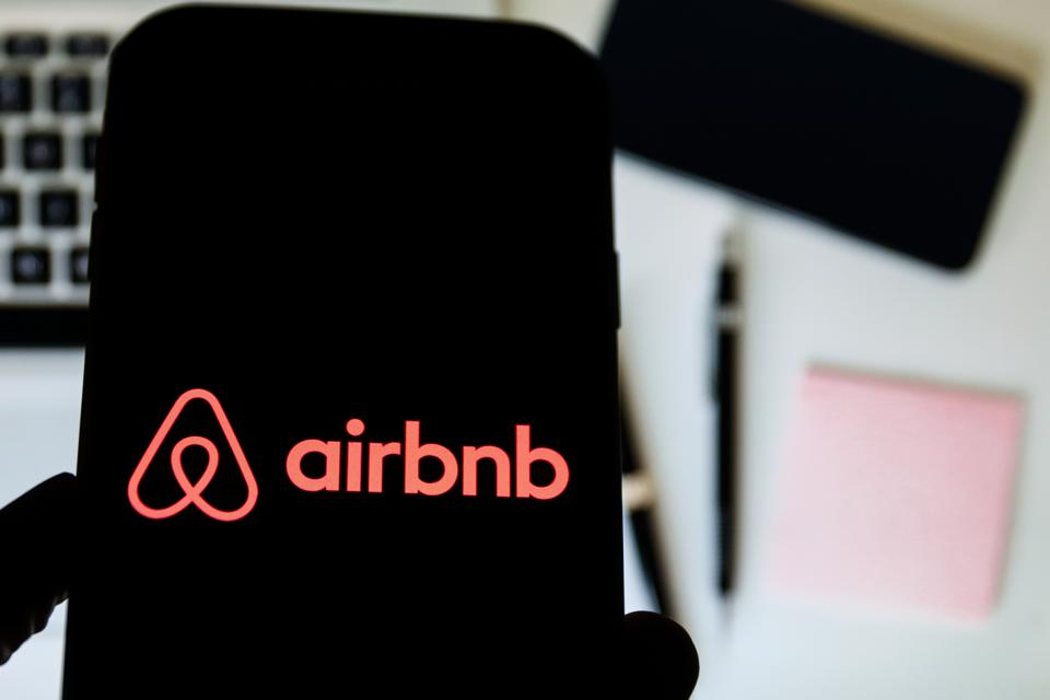 In this photo illustration a Airbnb company logo seen...
