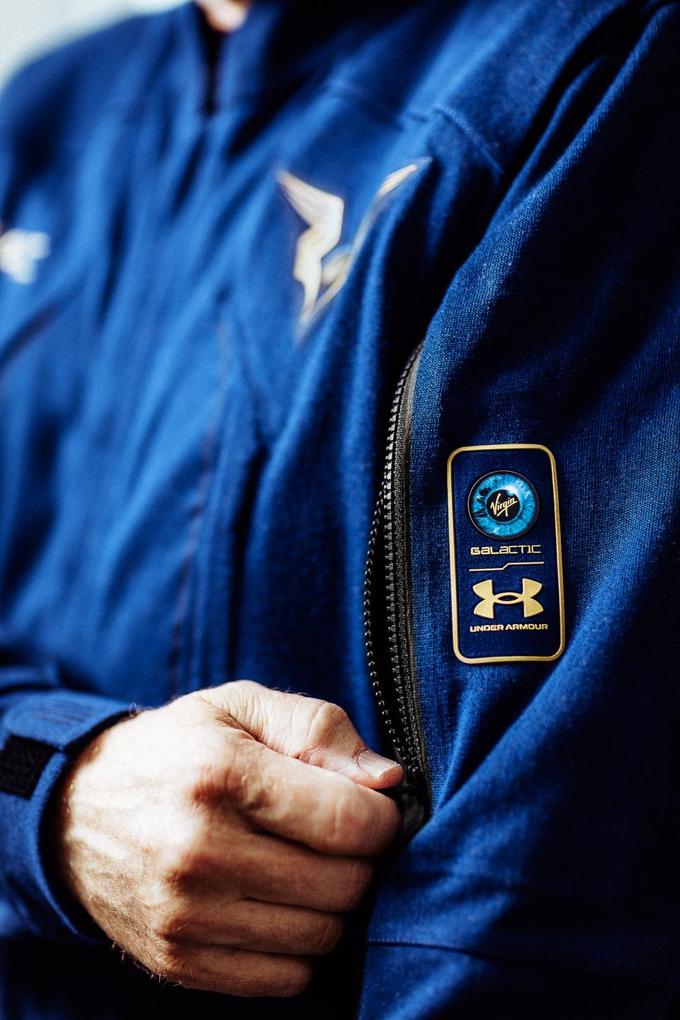 A pilot zips up a pocket on the sleeve of their space suit.