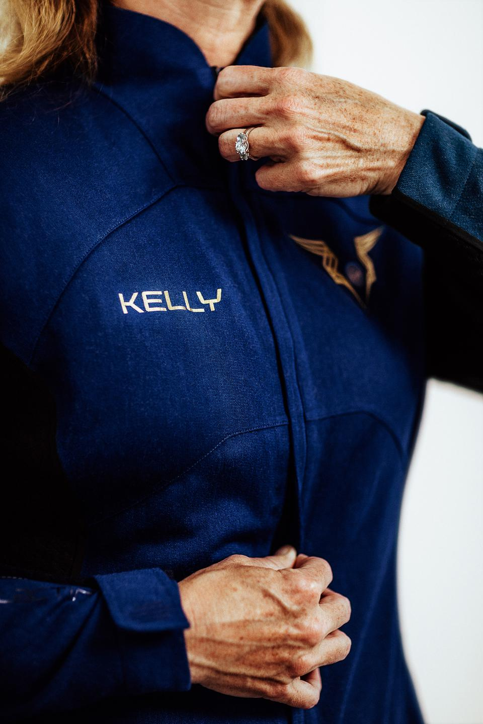 A woman zips up a spacesuit that reads ″Kelly″ on the chest.