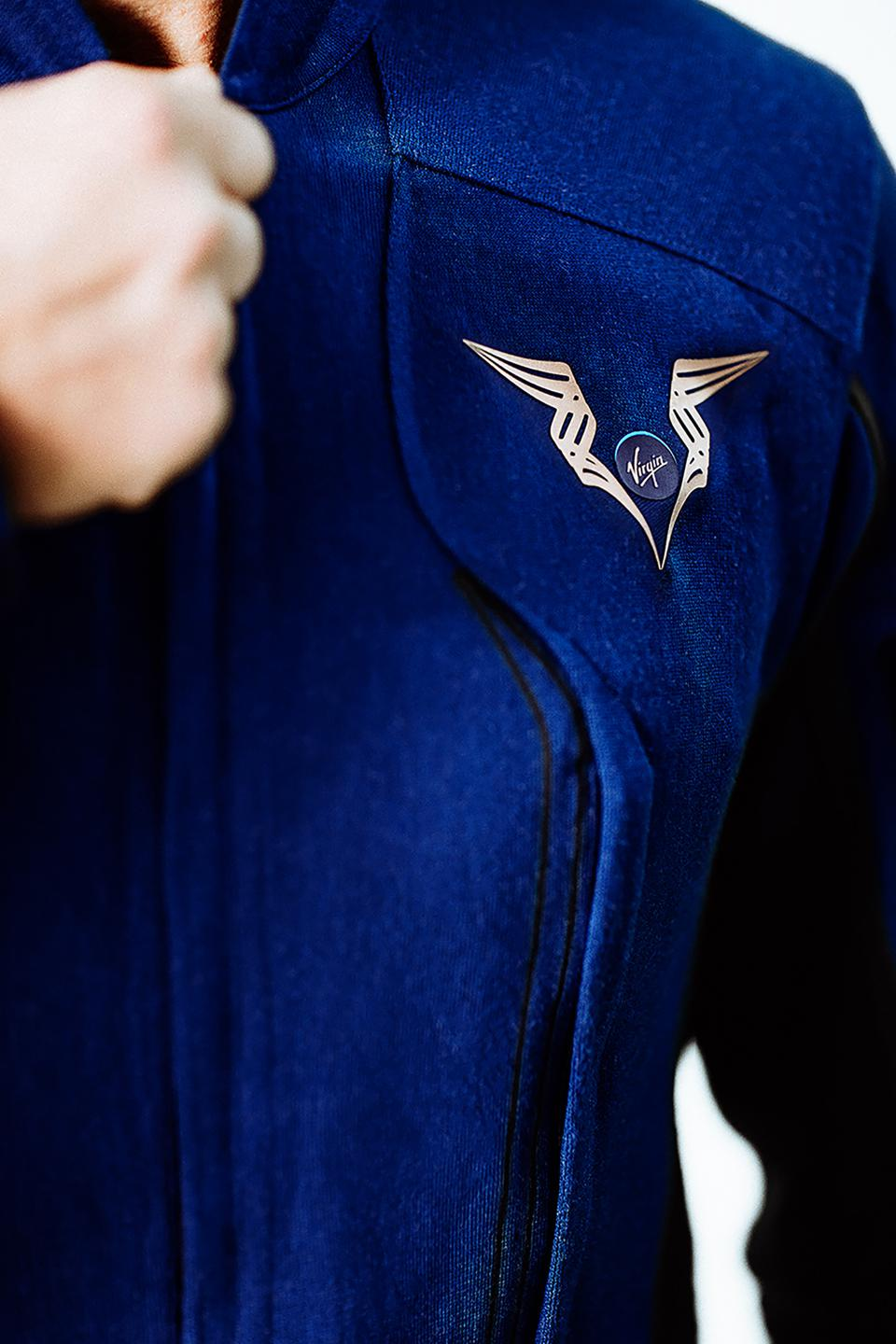 A Virgin Galactic emblem is shown as a pilot zips up their spacesuit.