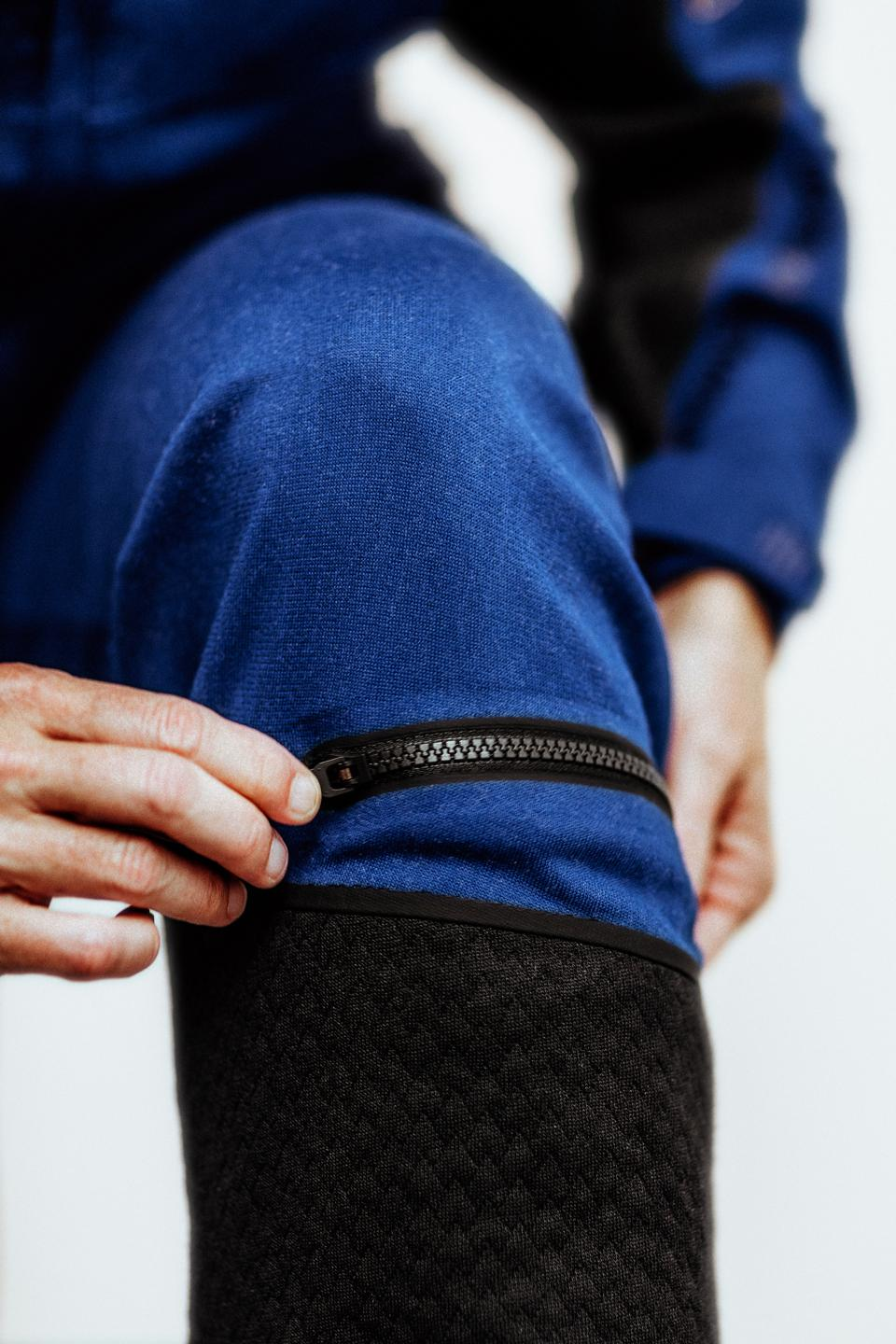A pilot zips a zipper located just below their knee on the spacesuit.