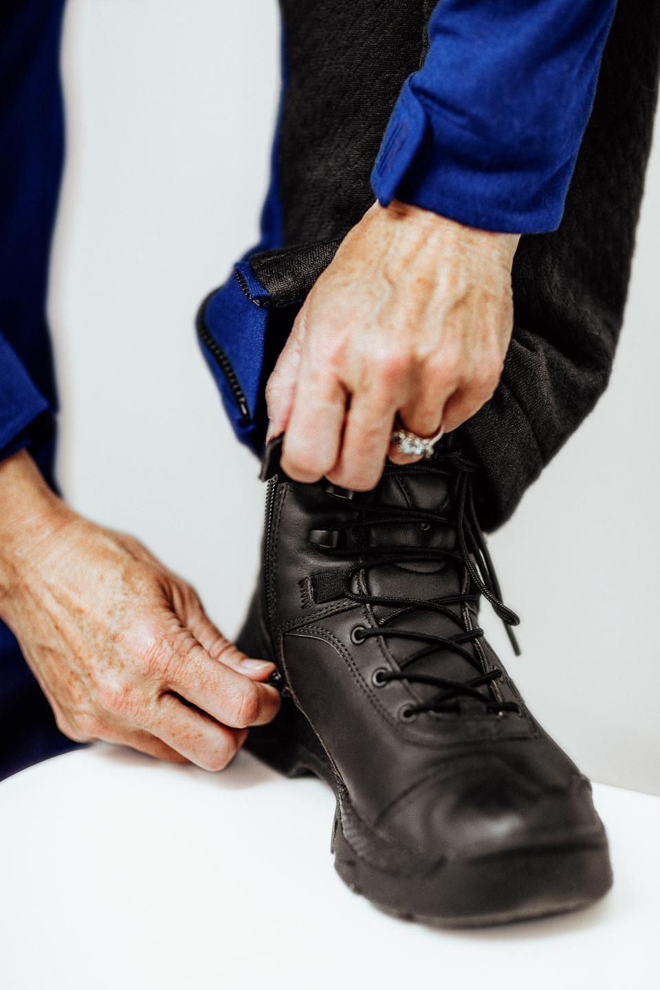 A pilot ties on a boot.