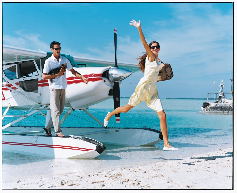 Model waving and man with dog on beach with seaplane
