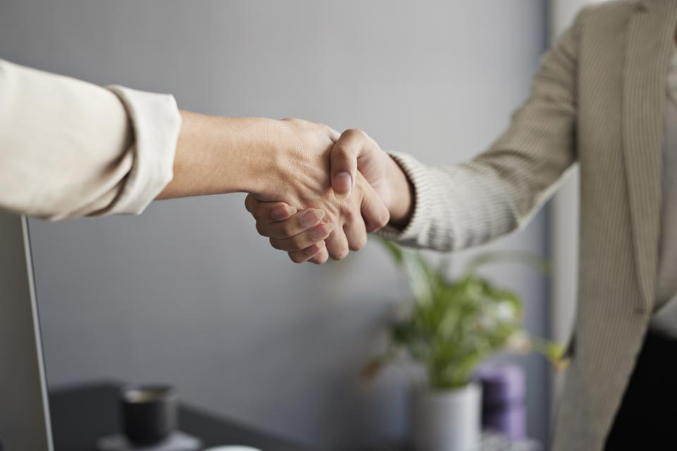 Female entrepreneurs shaking hands at workplace