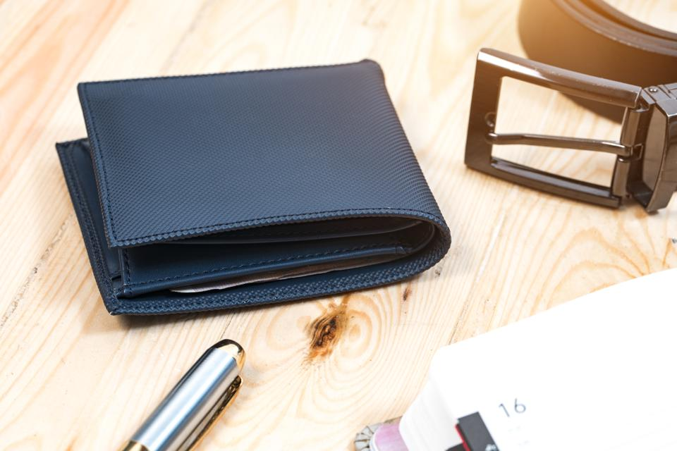 Documents, pen, belt and a leather wallet on a wooden desk. hotel table or gentleman's desk. shallow depth of field.