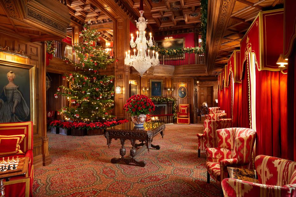The oak room at Ashford Castle in Ireland is lavishly decorated for Christmas with a tree.