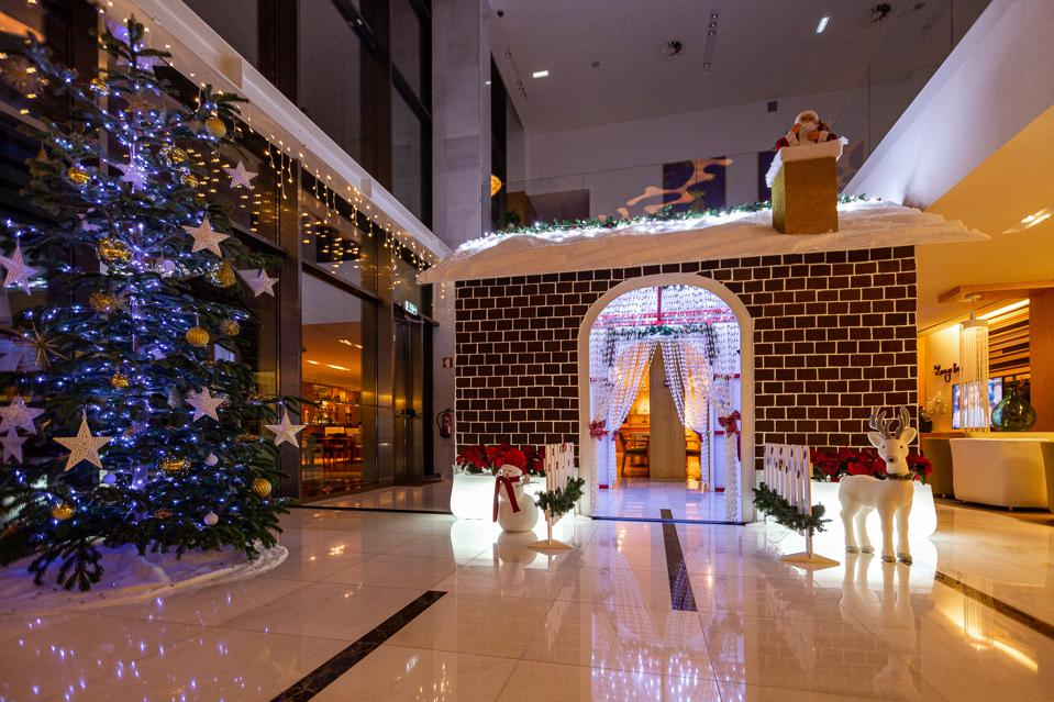 The lobby of Martinhal Cascais in Portugal is decorated with a Christmas tree and snowmen.