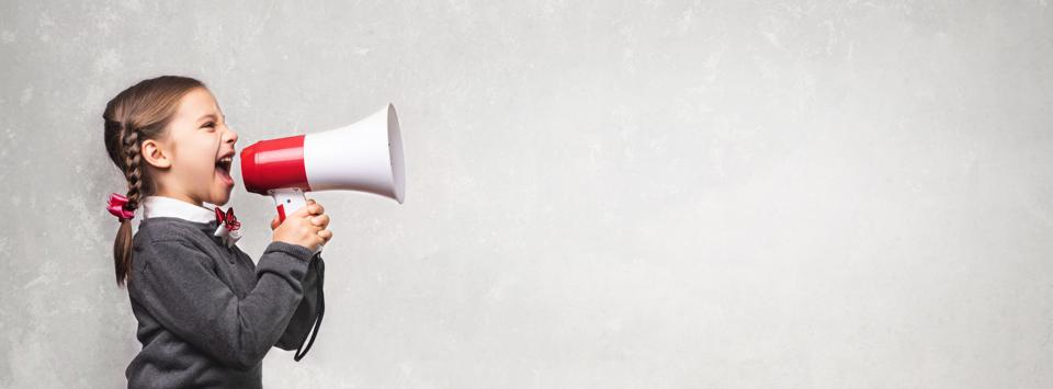 Child Girl Student Shouting Through Megaphone on Grey Backdrop with Available Copy Space. Back to School Concept.